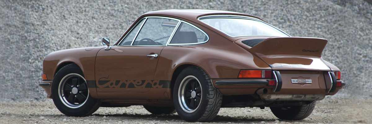 A brown Porsche 911 Carrera RS on gravel