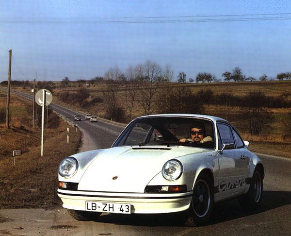 A German 1973 911 RS 2.7 with black striping. The driver is wearing matching clothes.